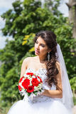 Young bride in wedding dress holding bouquet Stock Image