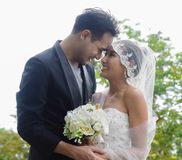 Young bride in white dress and groom in suit standing in garden with head to head wedding theme stock photography