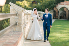 Young bride in white dress and groom walking holding hands near old castle Stock Image
