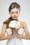 A young bride in a white dress holding flowers Royalty Free Stock Photography