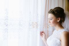 Young bride in white dress looking out the window. Royalty Free Stock Photography