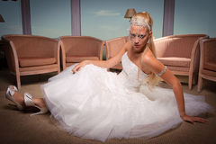 Young bride in white dress seated on the floor. Royalty Free Stock Image