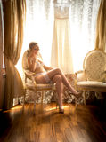 Young bride in white lingerie posing on chair at hotel room Stock Images
