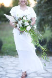 Young bride in white wedding dress holding beautiful bouquet Stock Photography