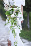 Young bride in white wedding dress holding beautiful bouquet Royalty Free Stock Photos