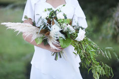 Young bride in white wedding dress holding beautiful bouquet Stock Photo