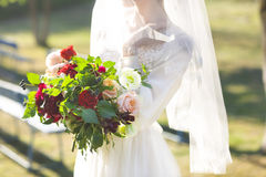 Young bride in white wedding dress holding beautiful bouquet Royalty Free Stock Images