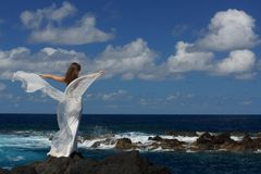 Young fiancee with white wings of wedding dress on rock sea shore on Sao Miguel island, Azores