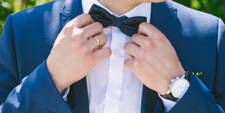 Young bridegroom dressing up and adjusting bowtie Stock Photography