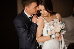 Young bridegroom gently hugs his charming bride with a bouquet. Stylish young bridegroom gently hugs his charming brunette bride with a bouquet of romantic roses royalty free stock photo