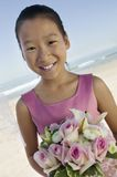 Young Bridesmaid with flowers on beach (portrait) Stock Image