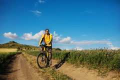 Young bright man on mountain bike. On a rural background Royalty Free Stock Photo
