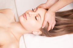 Young bright woman receiving head massage Royalty Free Stock Image