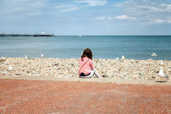 Young British woman sitting on Llandudno promenade looking out t Royalty Free Stock Image