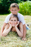 Young brother and elder sister or mother & son smiling together on dry hay on summer day Stock Image