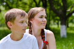 Young brother and elder sister sitting in green summer garden and looking in same direction Stock Photo