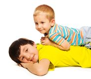 Young brother laying on the back of bigger Royalty Free Stock Image