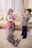 Young brother and sister arguing, girl using vacuum cleaner and Royalty Free Stock Photo