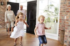 Young brother and sister arriving home with grandparents royalty free stock image
