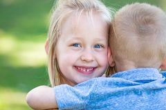 Young Brother and Sister Hugging Outdoors royalty free stock photo