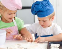 Young brother and sister kneading a dough Royalty Free Stock Photos