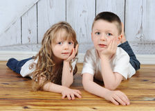 Young brother and sister laying together in floor Royalty Free Stock Image