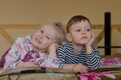 Young brother and sister lying on a bed together Royalty Free Stock Photo