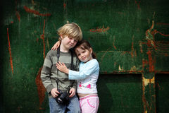 Young brother and sister pose for a photo. Two young children stand still while they have their photo taken against a grunge background whilst holding a camera Stock Photo