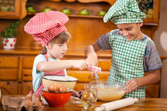 Young brother and sister preparing ingredients for making cakes Royalty Free Stock Image