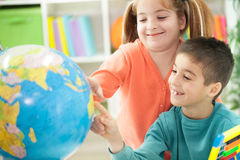 Young brother sister shows place on the globe Royalty Free Stock Images