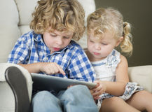Young Brother and Sister Using Their Computer Tablet Together Royalty Free Stock Photos