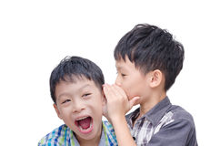 Young brother whispering his twin Royalty Free Stock Image