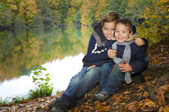 Young brothers in autumn forest. Two young brothers happy smiling at forest lake in autumn Royalty Free Stock Photos
