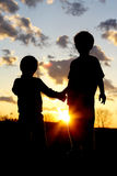 Young Brothers Holding Hands in Front of Sunset Royalty Free Stock Photos