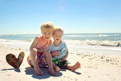 Young Brothers Hugging on Beach by Ocean. A young child and his baby brother are sitting on the beach in front of the ocean, hugging eachother and sitting by a stock photo
