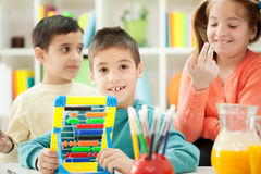 Young brothers and sisters together  learn math on abacus Royalty Free Stock Images