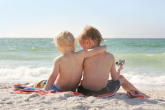 Young Brothers Sitting on Beach By Ocean with Arms Around Each O. Two young children, a boy and his little brother, are sitting in the white sand at the beach by stock photo