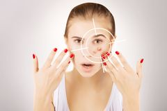Girl fights ugly skin, grey gradient background. Young broun eyed blond model fights with pimples,target on her face royalty free stock photo