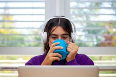 Young brown girl with headphones and a cup in her hands watches her computer screen in an office stock photos