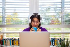Young brown girl with headphones and a cup in her hands watches her computer screen in an office royalty free stock images
