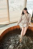 Brunette woman relaxing in jacuzzi in spa center with panoramic windows. Young brown-haired caucasian happy woman getting spa treatment at beauty salon, taking royalty free stock photo