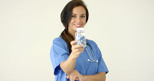 Young brown haired doctor in scrubs holds bottle Stock Photos