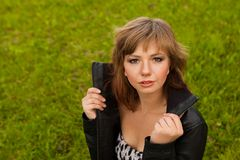 A young brown-haired girl on grass background Royalty Free Stock Images