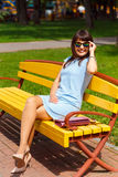 A young brown haired woman in blue dress. Sits on a park bench Stock Photo