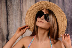 Young brown-haired woman with straw hat. On wooden background Royalty Free Stock Photo