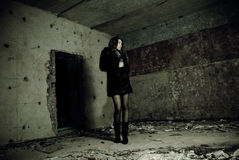 Young brunet at broken house. Young brunet woman standing at abandoned house room Royalty Free Stock Photos