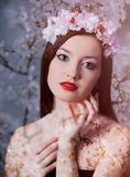Young brunet girl with wreath. On red background. Springtime style Royalty Free Stock Images