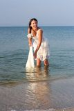 Young brunet woman in the blue water in wet white dress Royalty Free Stock Images