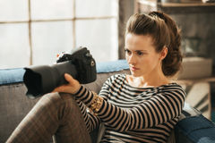 Young brunet woman is sitting and holding dslr camera. Young brunet woman is sitting on couch and holding dslr photo camera royalty free stock photography