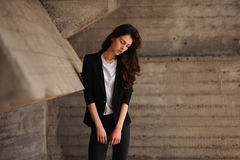 Young brunet woman standing outside in black jacket, jeans wearing hills . horizontal Royalty Free Stock Images